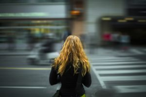 Woman facing road with traffic